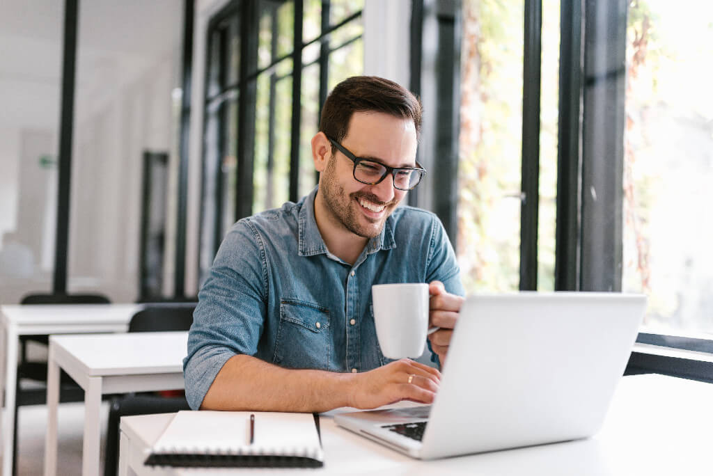 A laughing man looking at his laptop and holding a cup of coffee