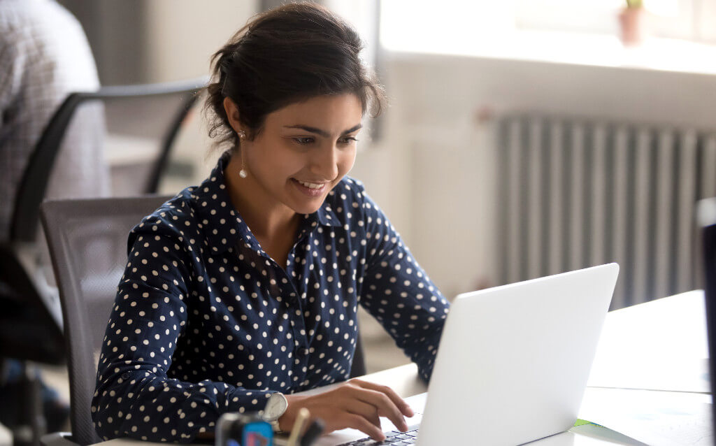 A smiling woman looking at her laptop screen