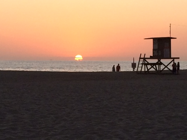 sunset on the beach with lifeguard stand