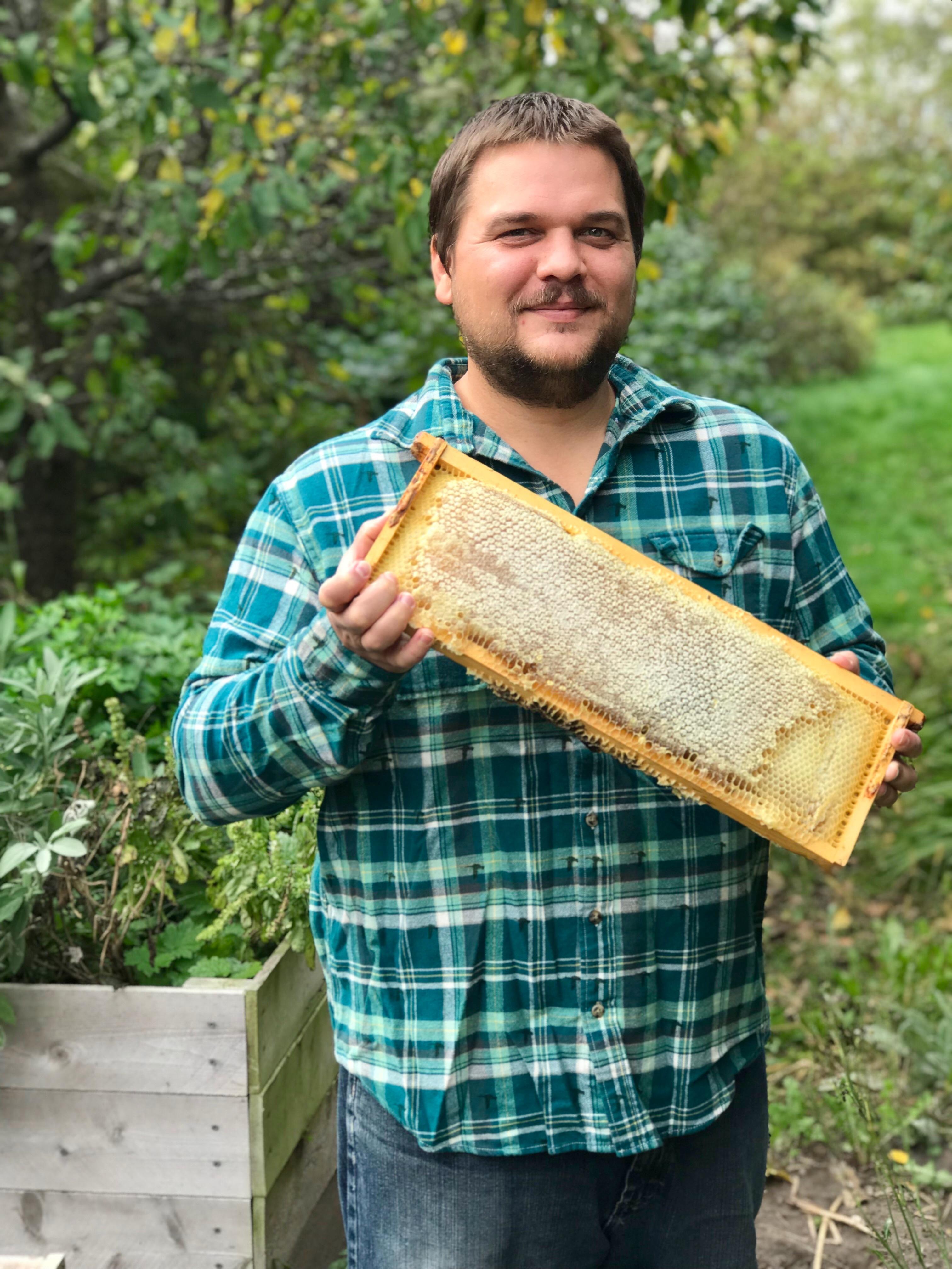 Karl harvesting honey on the homestead