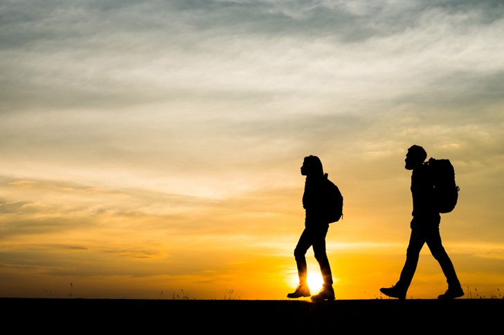 Two hikers appear as silhouettes with the sun rising behind them.