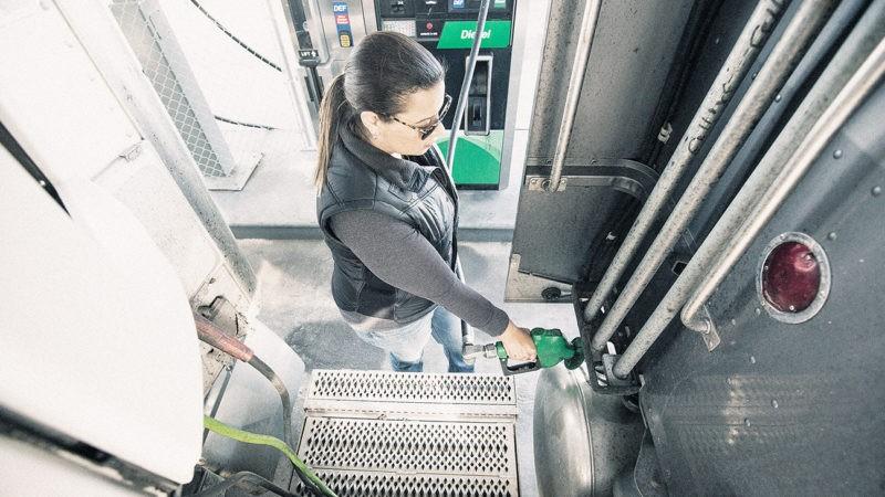 Female truck driver fills her tank
