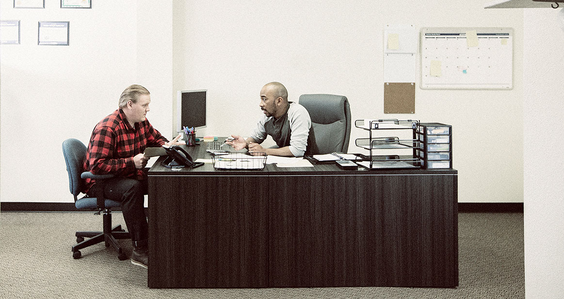 employee speaking with manager in office