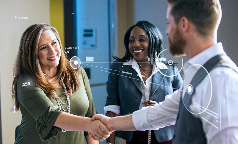 politician shakes hands while digital information swirls around
