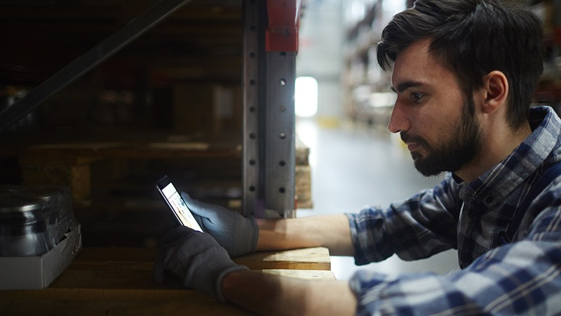 man in warehouse looks at smart phone