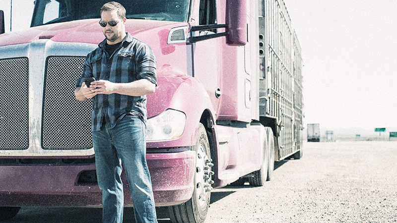 truck driver stands ion front of his truck looking down at his mobile device
