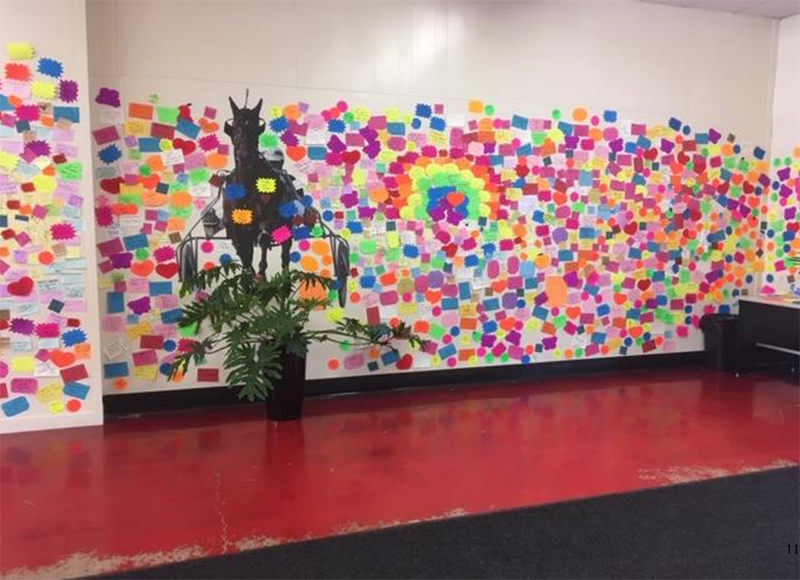 "The Gratitude Wall at Scarborough Downs as described by WEXer Charity Hirst: ""There is a wall of post-it notes that grows daily, thank you notes left by grateful recipients of their COVID vaccine. Reading these hundreds of messages of gratitude and hope moves me to tears every time."""
